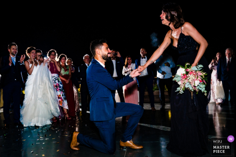 A man proposes to a woman during this Spain wedding as the bride and groom watch in this photo by a Ho Chi Minh, Vietnam wedding photographer.