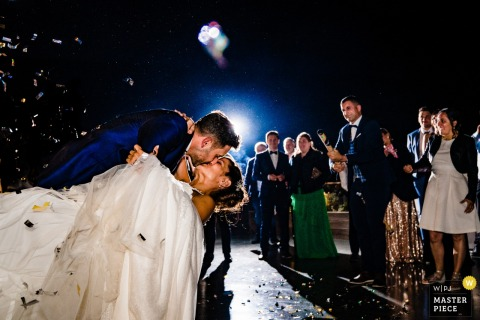The groom dips his bride and kisses her as confetti falls around them at their Spain wedding in this photo by a Ho Chi Minh, Vietnam wedding photographer.