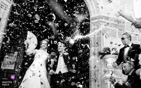 Black and white photo of the bride and groom exiting the church as guests toss confetti by a Murcia, Spain wedding photographer.