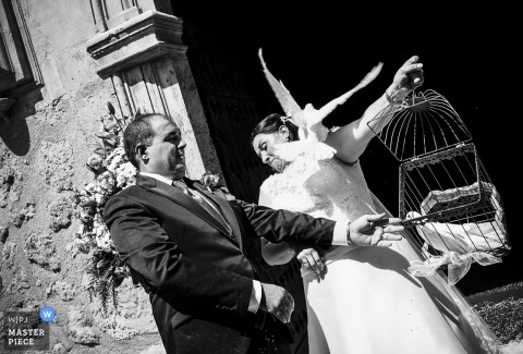 Black and white photo of the bride and groom releasing a white dove from its cage outside the church by a Murcia, Spain wedding photographer.