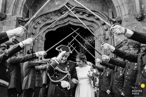 Photo noir et blanc du marié, vêtu de l'uniforme, et de son épouse marchant entre des soldats avec leurs épées relevées par un photographe de mariage à Madrid, en Espagne.