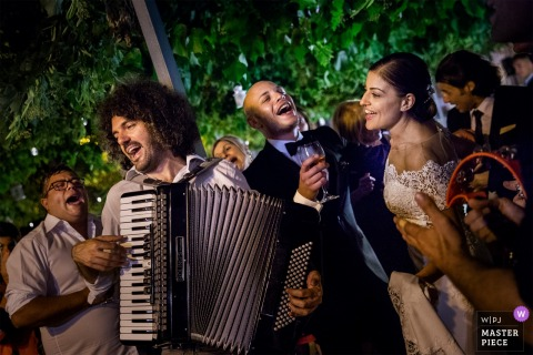 The bride and groom stand next to the accordionist as he plays outside in this photo by a Cosenza wedding photographer.