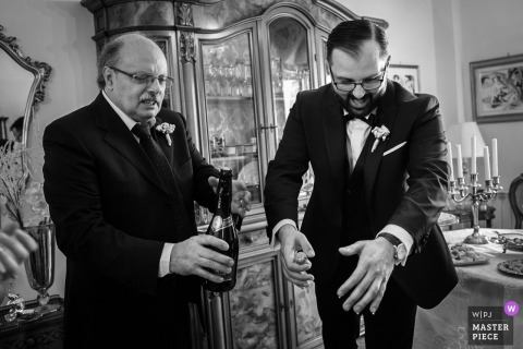 Zwart-witte foto van twee mannen die een fles champagne in een eetkamer openen door een Cosenza-huwelijksfotograaf.