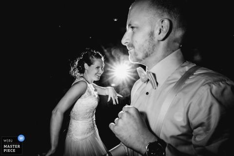 Schwarzweiss-Foto der Braut und des Bräutigams auf der Tanzfläche, während ein Lichtstrahl zwischen ihnen von einem Frankfurter Hochzeitsfotografen scheint.