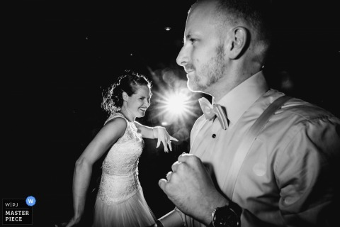 Black and white photo of the bride and groom on the dance floor as a beam of light shines between them by a Frankfurt wedding photographer.