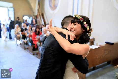 The bride waves as she and the groom hug each other in this photo by a Piedmont wedding photographer.