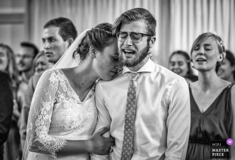 Black and white photo of the bride holding the groom and resting her head on his shoulder by a Nieuw-Vennep, Netherlands wedding photographer.