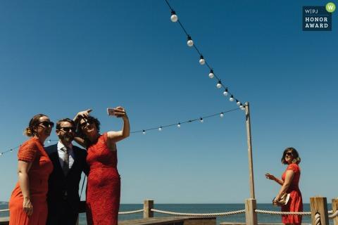 East Quay, Whitstable Brautjungfern in roten Kleidern Pose mit dem Gentleman für ein Selfie