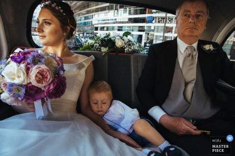 The bride sits in the back of a vehicle with a man and a young boy who has fallen asleep on her in this photo by a London, England wedding reportage photographer near the HAC, London.