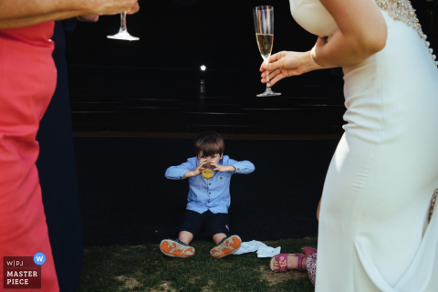 Photo taken at the RAC, Surrey between the bride and a guest of a boy sitting on the ground sipping a drink by a Surrey, England wedding reportage photographer.