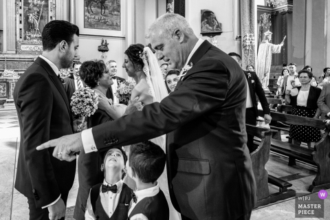Black and white photo of a man pointing as two young boys look up at him and the bride and groom stand in the background by a Sicily wedding photographer.