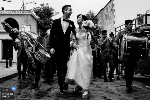 Oaxaca, Mexico wedding photo showing the bride and groom walking the streets with musicians.