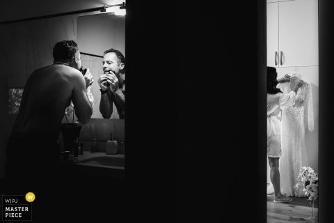 Black and white wedding photography showing bride and groom getting ready together.