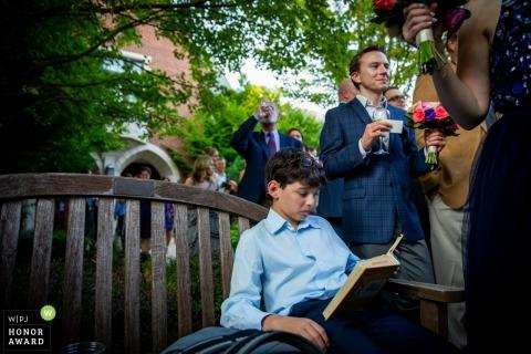 Winnetka, Illinois, réception de mariage en plein air - un jeune garçon lit un livre entouré de convives