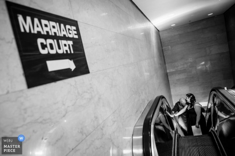 Photographie du mariage à la cour du mariage de Chicago d'un couple qui monte un escalator - photographie de mariage en noir et blanc.