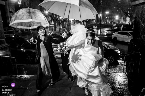 The bride is covered by umbrellas at night for her Rosario, Argentina wedding.