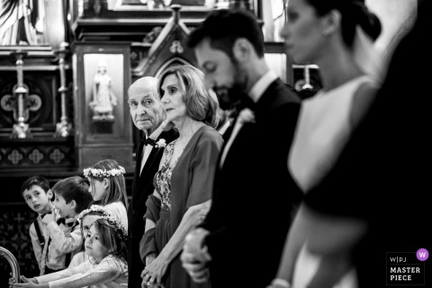 Black and white photo of the bride, groom, and wedding party standing together by a Rosario, Argentina wedding photographer.