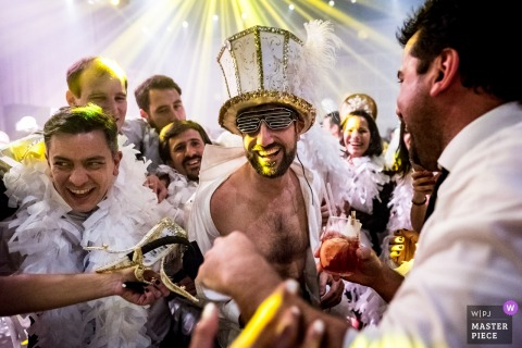 The groom wears a large hat and sunglasses surrounded by guests wearing white feather boas in this photo by a Rosario, Argentina wedding photographer.