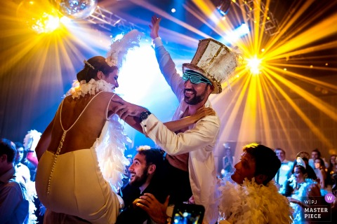 The bride and groom sit on guests' shoulders wearing feathers and a large hat as disco lights shine around them in this photo by a Rosario, Argentina wedding photographer.