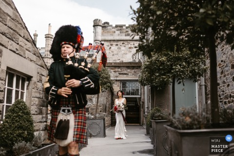 The bride stands holding her bouquet as a man playing the bagpipes walks ahead of her in Edinbugh, Scottland in this photo by a Los Angeles, CA wedding photographer.