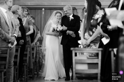 The bride walks down the aisle with her father in London, England in this black and white photo by a Los Angeles, CA wedding photographer.