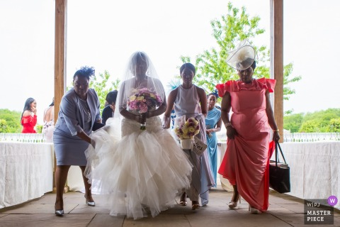 A woman helps the bride with her dress as she walks with three women in this photo by a London, England wedding reportage photographer.
