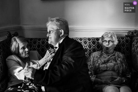 Czarno-białe zdjęcie dwóch kobiet siedzących na kanapie, jak jeden pomaga mężczyzna dostosować jego muszkę przez fotografa ślubnego reportażu z Essex w Wielkiej Brytanii.
