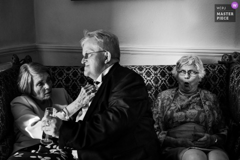 Black and white photo of two women sitting on a couch as one helps a man adjust his bow tie by an Essex, UK wedding reportage photographer.