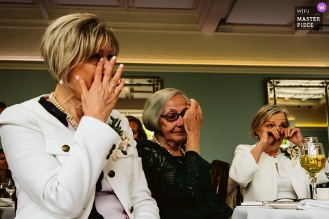 Three guests become tearful during the reception in this photo by a West Midlands, UK wedding reportage photographer.