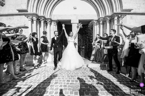 Black and white photo in Marseille, France of the bride and groom exiting the ceremony with arms raised as guests toss rice by a Miami, FL wedding photographer.