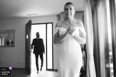 The bride makes a nervous face as she stands in her wedding dress and the groom walks in the door in this black and white photo by a Paris wedding photographer.
