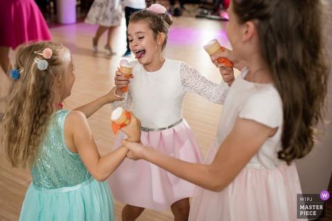 Drei junge Mädchen halten Hände in einem Kreis, während sie Eistüten in diesem Foto von einem Polen-Hochzeitsfotografen essen.