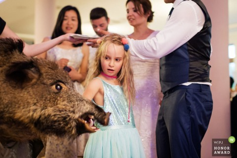 Little flower girl curious about taxidermy boar's head at this Poland wedding