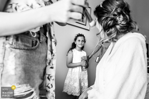 A young girl watches as the bride gets her makeup done in this black and white photo by a Romania wedding photographer.