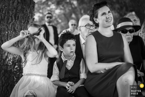 Black and white photo of guests during the ceremony with a young boy and girl holding her hair over her face by a Loire-Atlantique, France wedding photographer.