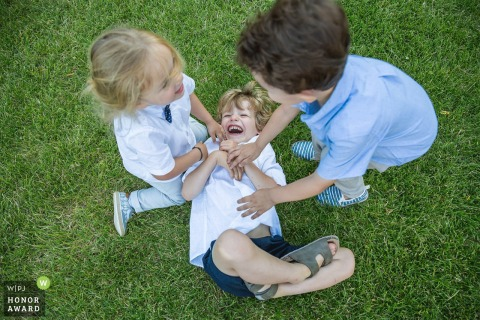 Frankrijk kinderen spelen - kinderen kietelen een jongen op het gras bij de bruiloft receptie