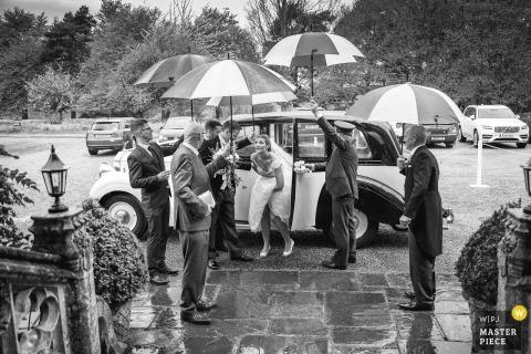 Novia bajo paraguas durante Lucky Rain en Sussex