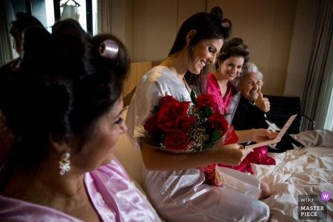 The bride sits with her bridesmaids holding a bouquet of roses and reading a card in this photo by a São Paulo, Brazil wedding photographer.