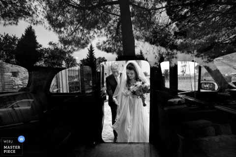 Black and white photo of the bride preparing to enter a vehicle with trees reflected on its surface by a Calabria wedding photographer.