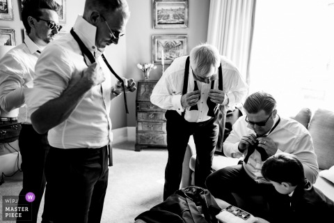 The groomsmen work on tying their bow ties in this black and white photo by a Dublin, Ireland wedding reportage photographer.
