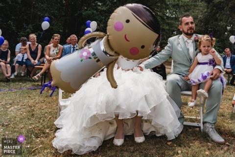 Een ballon vervangt het gezicht van de bruid terwijl een jong meisje op de schoot van de bruidegom op deze foto zit door een Nederlandse huwelijksfotograaf.