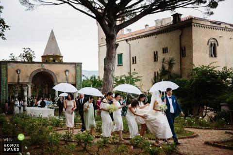 Ravello-Brautparty, die versucht, trocken zu bleiben - regnerische Hochzeit mit Regenschirmen