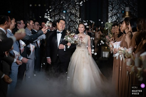 The bride and groom exit the ceremony past their guests through mist in this photo by a Bangkok, Thailand wedding photographer.