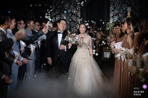 De bruid en de bruidegom verlaten de ceremonie voorbij hun gasten door mist in deze foto door een het huwelijksfotograaf van Bangkok, Thailand.