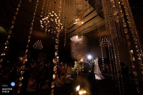De bruid en de bruidegom bevinden zich bij het altaar omringd door hangende kristallen en kroonluchters in deze foto door een het huwelijksfotograaf van Bangkok, Thailand.