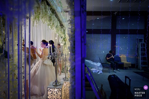 A photo split by a wall with a guest sitting alone on one side and the wedding party celebrating on the other by a Bangkok, Thailand wedding photographer.