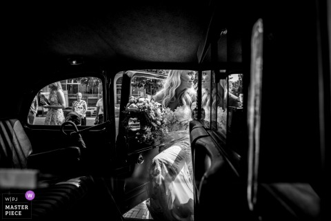 Black and white photo of the bride preparing to enter a vehicle by an Oldenzaal, Netherlands wedding photographer.