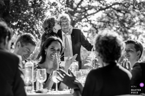 Black and white photo of guests applauding as the bride kisses her father's cheek by a Delden, Netherlands wedding photographer.