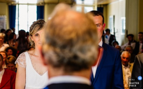 Photo taken behind the officiator as the bride and groom stand at the altar during the ceremony by a Laruns, France wedding photographer.