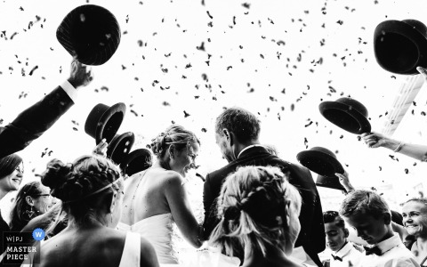 Black and white photo of guests waving bowler hats and tossing flower petals at the bride and groom by a Mende, France wedding photographer.